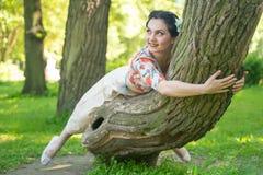 Hübsche nette junge brunette Frau, die mit ihrem reizenden Baum im grünen Sommergarten allein aufwirft glückliches Mädchenvergnüg lizenzfreie stockfotos