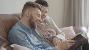 Hübsche Oma des Porträts und erwachsener Enkel, die zu Hause aufpassende alte Fotos im großen Fotoalbum sitzt Familie erinnern si stock video footage