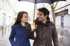 Hübsche Paare unter dem Regen auf Straße Stockbild