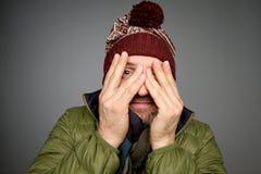 Hübsche reife Mannbedeckung mustert mit den Händen, während stehender grauer Hintergrund im warmen Winter kleidet lizenzfreie stockfotos