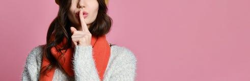 Hübsche reizend junge Frau, die geheimen Weileholdingfinger auf Lippen hat und Ruhezeichen zeigt stockfotografie