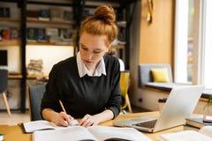 Hübsche rote behaarte Jugendliche, die Laptop-Computer verwendet lizenzfreie stockfotografie