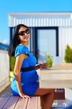 Hübsche, schwangere Frau im Café mit neuem Getränk stockfoto