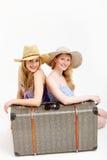 Hübsche Schwestern, die mit einem geteilten Koffer reisen Lizenzfreie Stockfotos