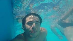 Hübsche Schwimmen des jungen Mannes im Pool, Unterwasserschuß