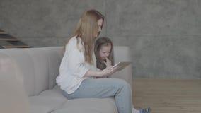 Hübsche smilling junge Mutter des Porträts und ihre entzückende nette kleine Tochter verwenden eine Tablette und ein Lächeln und  stock footage