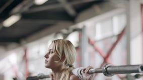 Hübsche Sportlerin, die mit Barbell an bodybuildendem Training in der Turnhalle hockt stock video footage