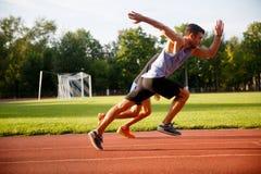 Hübsche starke laufende Männer auf spezieller rüttelnder Bahn Stockbilder