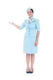 Hübsche Stewardess, die mit der Hand darstellt Stockbild