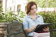 Hübsche Studentin Outside auf Bank unter Verwendung der Noten-Tablette lizenzfreie stockbilder