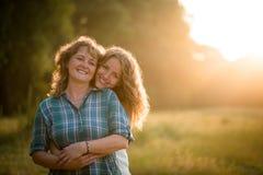 Hübsche Tochter, die ihre liebevolle Mutter von hinten umfasst Stockbild
