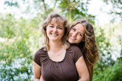 Hübsche Tochter, die ihre liebevolle Mutter von hinten umfasst Stockfotografie
