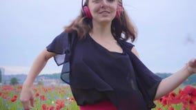 Hübsche tragende Kopfhörer der jungen Frau, die Musik hören und auf einem Mohnblumengebiet glücklich lächelt tanzen Verbindung mi stock video