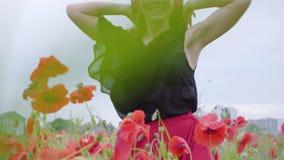 Hübsche tragende Kopfhörer der jungen Frau, die Musik hören und auf einem Mohnblumengebiet glücklich lächelt tanzen Verbindung mi stock footage