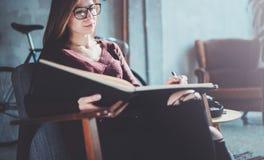 Hübsche tragende zufällige Kleidung der Gläser des jungen Mädchens, die Buchhände hält Blondes Sitzen der Frau im Weinleselehnses Lizenzfreie Stockfotos