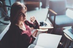 Hübsche tragende zufällige Kleidung der Gläser des jungen Mädchens, die Buchhände hält Blondes Sitzen der Frau im Weinleselehnses Lizenzfreies Stockbild