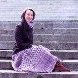 Hübsche und elegante Frau, die auf den Treppen sitzt Stockfoto