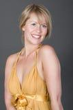 Hübsche und glückliche Blondine im goldenen Kleid Lizenzfreie Stockbilder