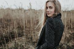 Hübsche und junge Frau mit dem langen blonden Haar kleidete im Wollmantel an, der Kamera über ihrer Schulter und Lächeln betracht Stockbild