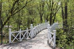 Hübsche weiße hölzerne Fußgängerbrücke über Strom in allgemeinem Park Domaine Maizerets während sonnigen Frühling afternoo stockfotografie