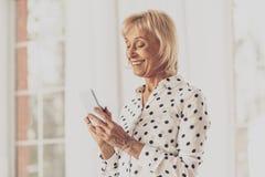 Hübsche weibliche Person unter Verwendung ihres Telefons lizenzfreie stockfotos