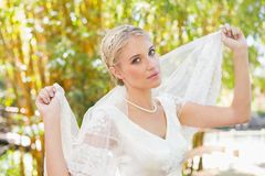Hübsche zufriedene blonde Braut, die ihren Schleier heraus lächelt an der Kamera hält Lizenzfreie Stockfotos