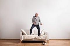 Hübscher älterer Mann, der auf der Couch, tanzend steht Schönes Tanzen der jungen Frau der Paare Stockfoto
