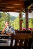 Hübscher älterer Mann, der seinen Morgenkaffee genießt Stockbild