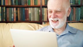 Hübscher älterer älterer Mann, der zu Hause an Laptop-Computer arbeitet Empfangene gute Nachrichten aufgeregt und glücklich stock video footage