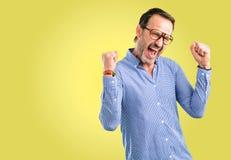 Hübscher älterer Mann lokalisiert über gelbem Hintergrund lizenzfreies stockbild