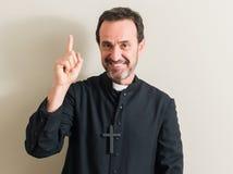 Hübscher älterer Priester zu Hause lizenzfreies stockbild