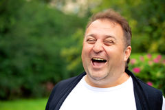 Hübscher überladener Mann, der im Freien lächelt und sich entspannt Stockfotos