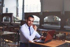 Hübscher überzeugter junger Geschäftsmann, der an Laptop am Café, Aufflackernlicht arbeitet Kaffeepause, Geschäftskonzept stockbilder