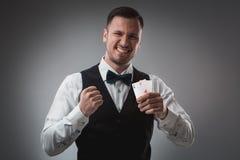 Hübscher überzeugter Mann, der die Karten betrachten Kamera hält Lizenzfreie Stockfotografie