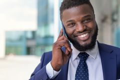 Hübscher afrikanischer Geschäftsmann in der Klage, die draußen am Telefon spricht Kopieren Sie Platz lizenzfreie stockbilder