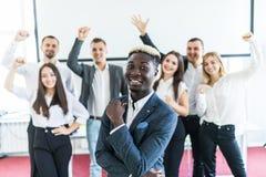 Hübscher afrikanischer Geschäftsmann vor Gruppe des Feierns von Wirtschaftlern auf Hintergrund stockfotografie