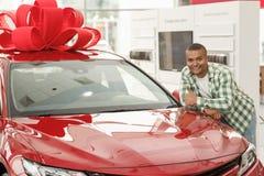 Hübscher afrikanischer Mann, der Neuwagen an der Verkaufsstelle wählt stockfotos