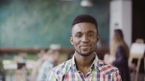 Hübscher afrikanischer Mann im beschäftigten modernen Büro Porträt des jungen erfolgreichen Mannes, der Kamera und das Lächeln be Stockbild