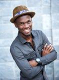 Hübscher Afroamerikanermann, der mit den Armen gekreuzt lächelt Stockbilder