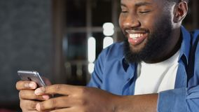 Hübscher Afroamerikanermann, der mit Freundin im App auf Smartphone plaudert stock video