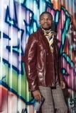 Hübscher Afroamerikanermann in der stilvollen Kleidung, die vor Graffitiwand aufwirft und einen Spray hält Lizenzfreies Stockfoto