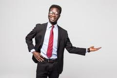 Hübscher Afroamerikanermann in einem schwarzen Anzug gestikulierend als ob, um eine Produktprobe auf Grau zu demonstrieren Stockbild