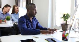 Hübscher afroer-amerikanisch Geschäftsmann, der im Büro arbeitet lizenzfreie stockfotos