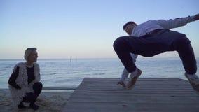 Hübscher asiatischer Kerl in der zufälligen Kleidung, die Breakdance vor seiner schönen kaukasischen Freundin auf dem Fluss tanzt stock video