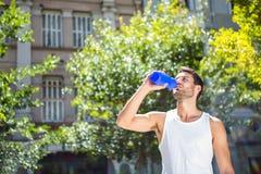 Hübscher Athlet, der aus Flasche heraus trinkt stockbilder