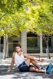 Hübscher Athlet, der sein Bein aus den Grund ausdehnt Lizenzfreie Stockfotos
