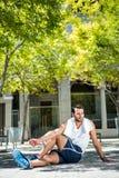Hübscher Athlet mit dem Tuch, das sein Bein aus den Grund ausdehnt Lizenzfreie Stockfotografie