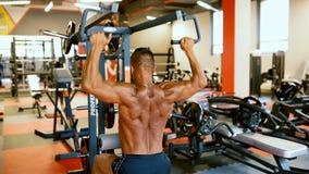 Hübscher Athlet trainiert in der Turnhallenmitte Hartes Training des Bodybuildermannes mischt an der Trainingsmaschine mit stock footage