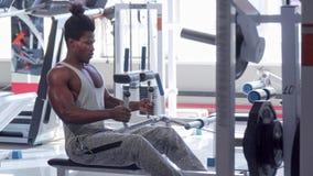 Hübscher athletischer afrikanischer Mann, der auf niedriger Reihensitzmaschine an der Turnhalle trainiert stock video