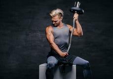 Hübscher, athletischer blonder Mann hält Barbell auf seiner Schulter Lizenzfreie Stockbilder